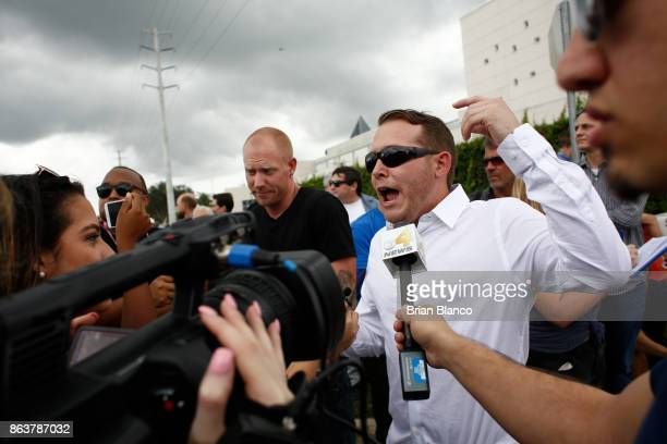 Selfdescribed white nationalist Tyler Tenbrink of Houston Texas left and friend William Fears speak to members of the media as demonstrators gather...