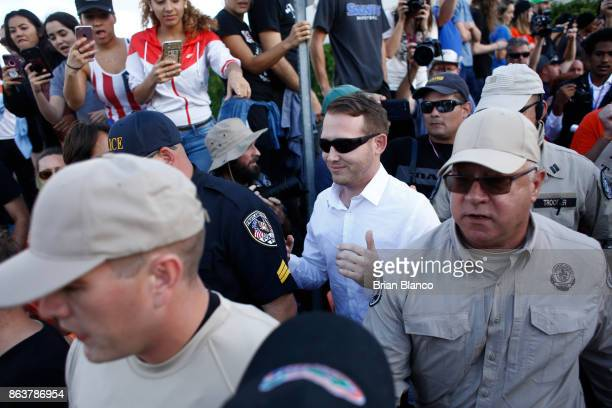Selfdescribed white nationalist William Fears of Pasadena Texas center walks behind Florida Highway Patrol troopers as the troopers assist his safe...