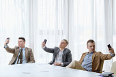 selfie addiction and inflated ego. successful business men taking photos of themselves. self-absorption narcissism and egomania concept