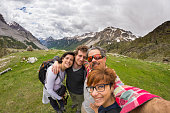 Four young people taking selfie on the Alps with snowcapped mountain range and dramatic sky in background. Scenic fisheye distortion. Concept of traveling people and nature beauty exploration.