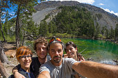 Four young people taking selfie in idyllic landscape with green lake, conifer woodland and mountains in background. Scenic fisheye distortion. Concept of traveling people and nature beauty exploration