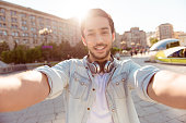 Selfie mania! Excited young guy is making selfie on a camera. He is wearing casual trendy wear and big headphones, on a walk in town outdoors