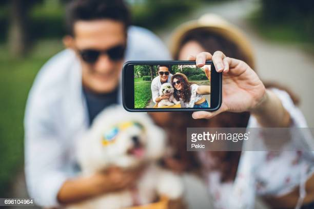 Selfie of couple and funny dog with sunglasses