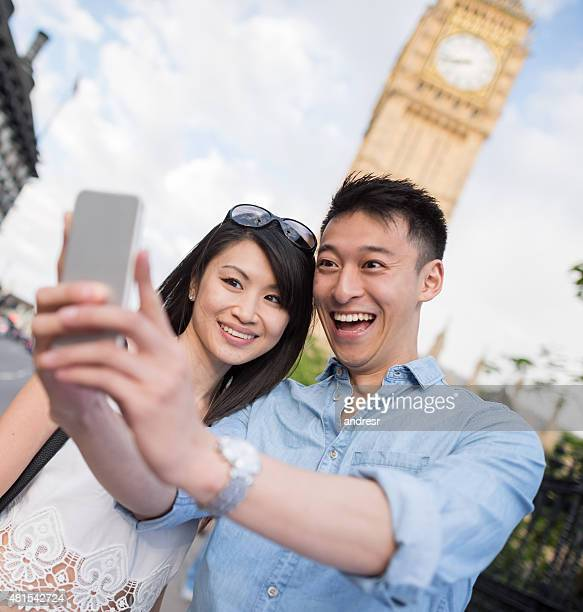 Selfie of happy Asian tourists in London