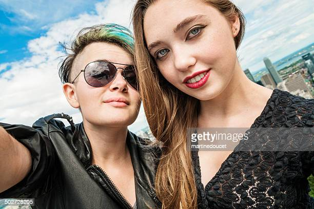 Selfie of two rebel teenages in front Montreal cityscape.