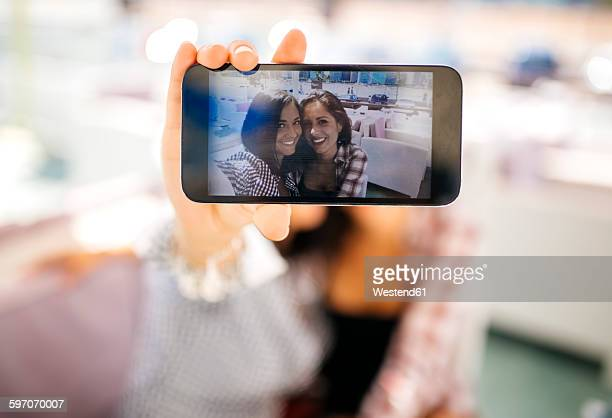 Selfie of two smiling female friends on cell phone display