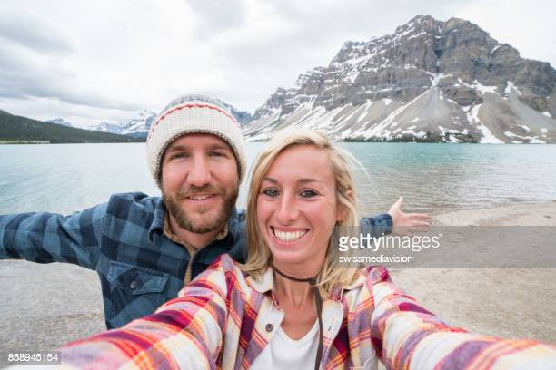 Selfie of young couple at mountain lake