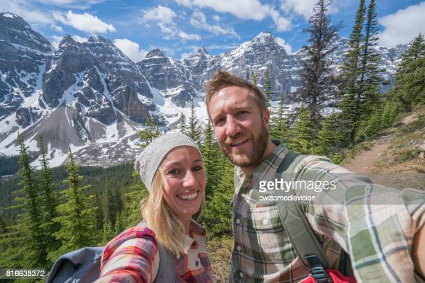 Selfie of young couple on mountain trail