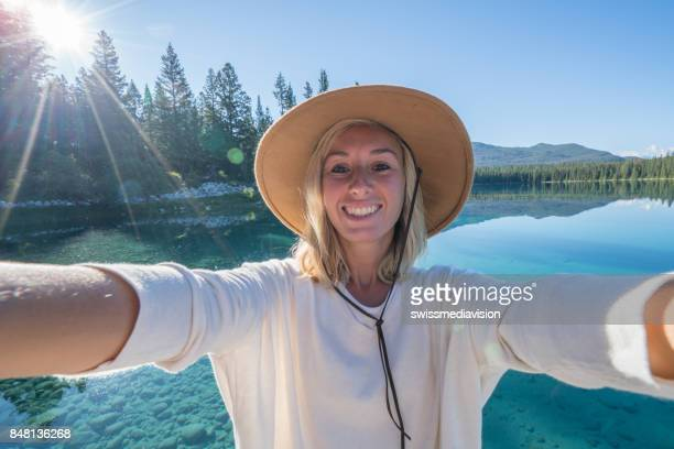 Selfie of young woman on lake at sunrise