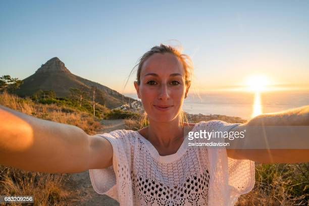 Selfie portrait of young woman, mountain and sunset