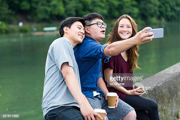 Selfie time! Group of friends taking selife near a lake