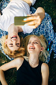 Two female friends lying on the grass at the park and taking selfie
