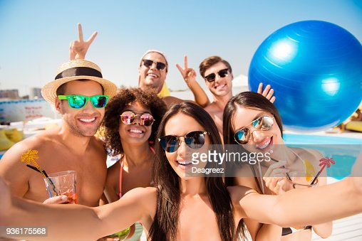 Selfie time! Six cheerful friends in fashionable different swim wear and sun protecting eyewear, caps, with drinks are posing for a selfie photo, that brunette lady is taking, beaming smiles, sunshine : Foto de stock