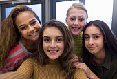 Four teenage students taking a selfie in school.