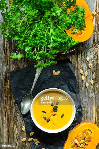 Selfmade pumpkin soup with pumpkin seeds and parsley on a wooden table