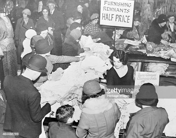 Selfridges during the Christmas sales Oxford Strreet London 1933 Shoppers crowd around tables of furnishing remnants that are being advertised as...