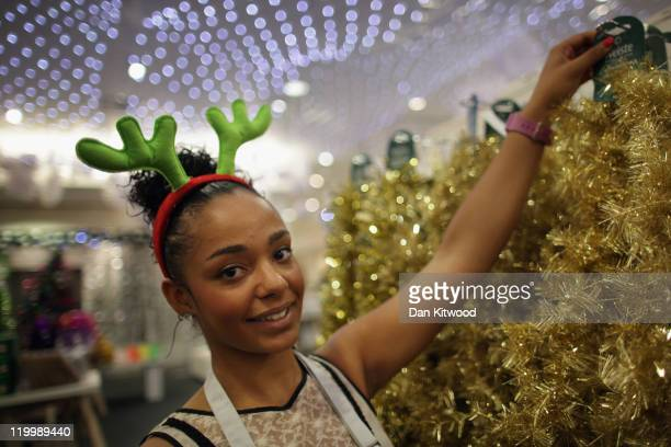 Selfridges employee Amber Dawson poses wearing antlers amongst decorations displayed in the Christmas shop at Selfridges department store on July 28...