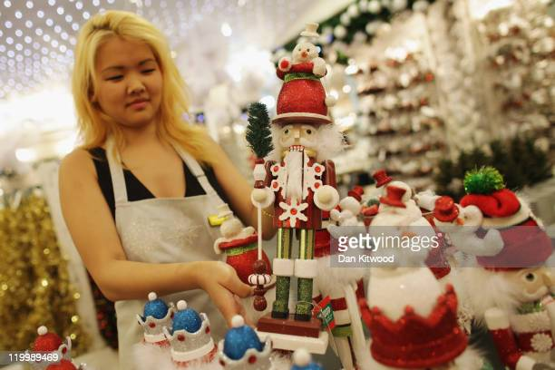 Selfridges employee Sara Sodnom holds a Christmas decoration on display in the Christmas shop at Selfridges department store on July 28 2011 in...