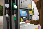 Self-service filling station. A man pays for fuel with a credit card