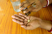 Self-treatment at home as per prescribed by doctor. Close up of a woman pouring medicine into her hand. Medical, health care or people concept. High Angel view. Close up with copy space room for text.