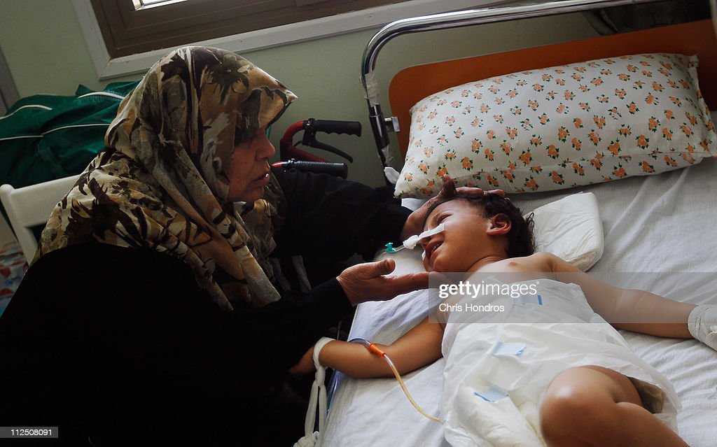 Selima Abdullah (L) caresses her youngest granddaughter Heba, who suffered a ripped-open abdomen from shrapnel, after an explosive shell landing near her home during fighting in the besieged city of Misrata two days earlier on April 19, 2011 at a hosptial in Misrata, Libya. Several families were all staying in a house in Misrata, as it was shelled today and some people were injured and taken to hospital as a result. As fighting continues between Libyan government forces and anti-government rebels, thousands of civilians are trapped in Misrata, Libya's third largest city, which has been under siege now for almost seven weeks with conditions showing no sign of improvement.