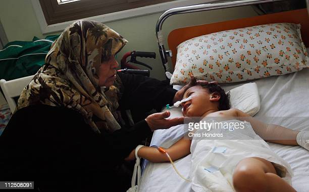 Selima Abdullah caresses her youngest granddaughter Heba who suffered a rippedopen abdomen from shrapnel after an explosive shell landing near her...