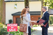 Seller congratulating young couple buying house in suburbs