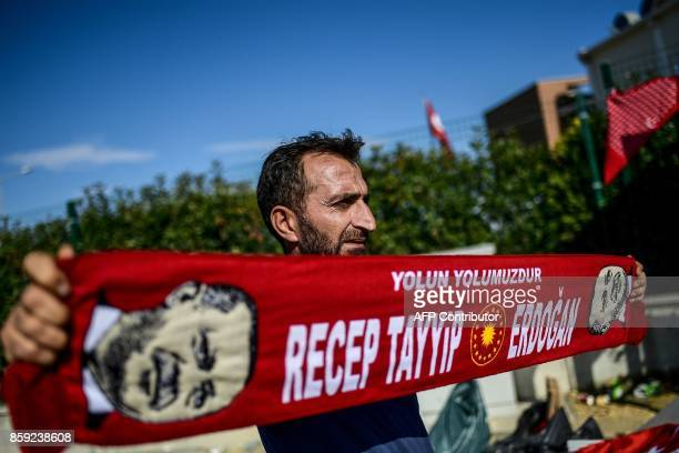 A seller holds a scarf picturing Turkish President Recep Tayyip Erdogan as he waits for customers by the Silivri prison courthouse in Istanbul on...