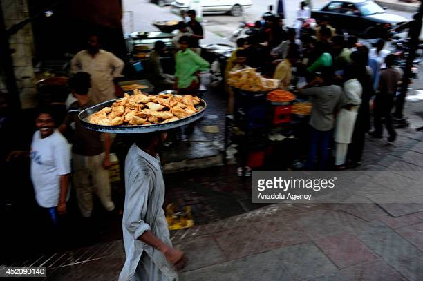 A seller holds cooked samosa traditional Pakistani food during Ramadan month in Islamabad Pakistan on 2 July 2014 Traditional foods are in demand on...