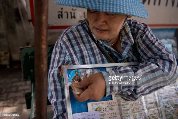 A seller of lottery tickets adjusts good luck charms on her lottery ticket board next to an image of Thai King Rama 5 at a park in Bangkok on August...