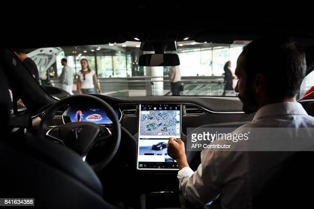 A seller shows the dashboard of the Tesla Model S car at the electric carmaker Tesla showroom of El Corte Ingles store in Lisbon on September 1 2017...