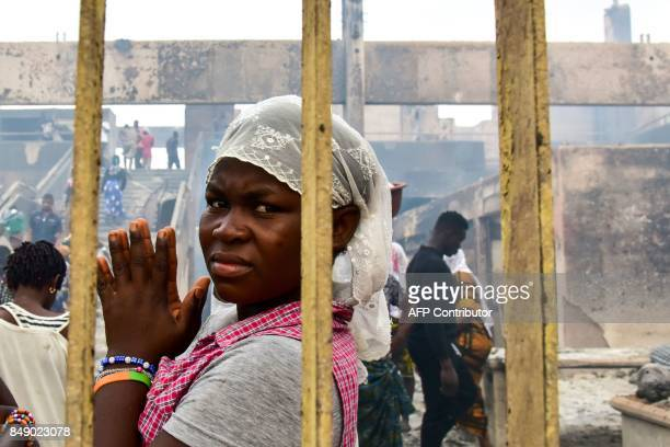 A seller stands next to her stall as sellers walk through debris in a market after a fire devastated the building overnight on September 18 2017 in...