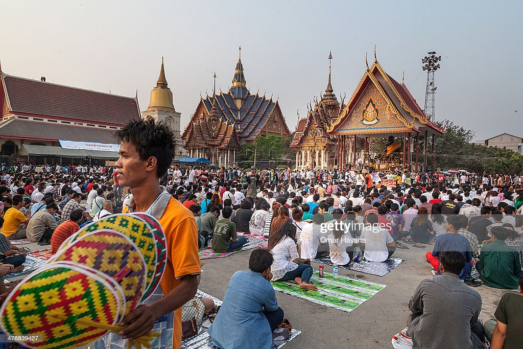 A seller walks between hundreds of Thai devotees during the celebration of the annual Tattoo festival at Wat Bang Phra on March 15 2014 in Nakhon...