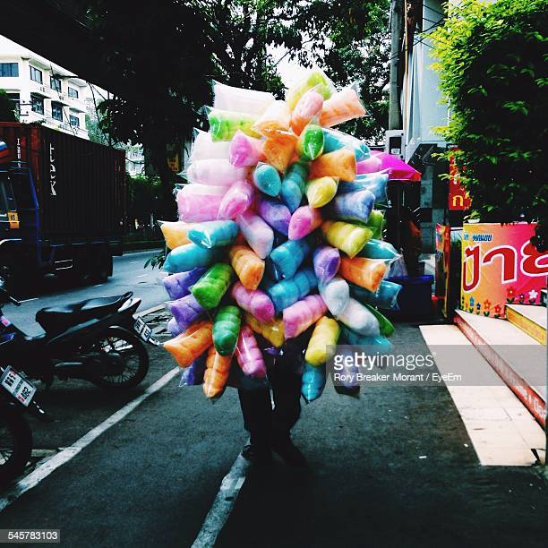 Seller With Multi Colored Candy Floss On Sidewalk