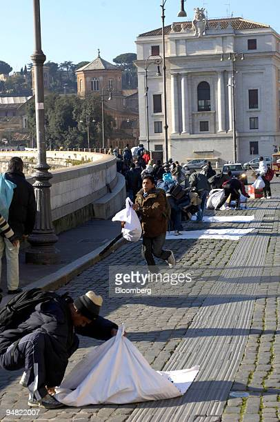 Sellers quickly wrap up their fake bags after the arrival of a police car near the Vatican in Rome Italy Thursday January 12 2006 Italy plans to...