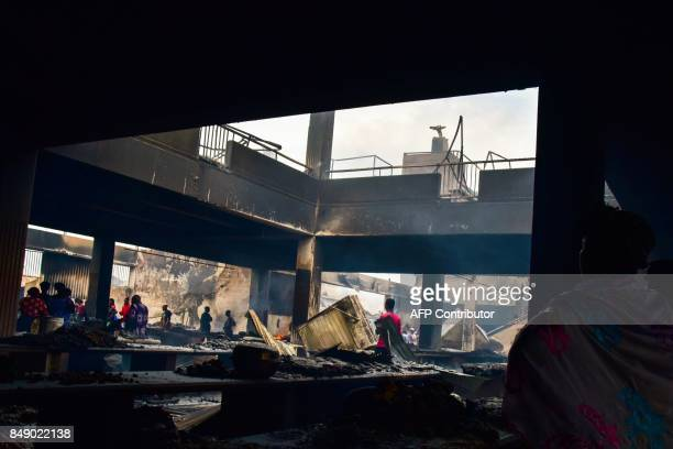 Sellers walk through debris in a market after a fire devastated the building overnight on September 18 2017 in the Abobo neighborhood of Abidjan /...