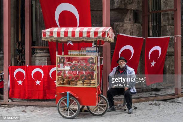 Selling  pretzel like  traditional simit and colorful turkish flag display in the background, Eminonu, Istanbul Turkey