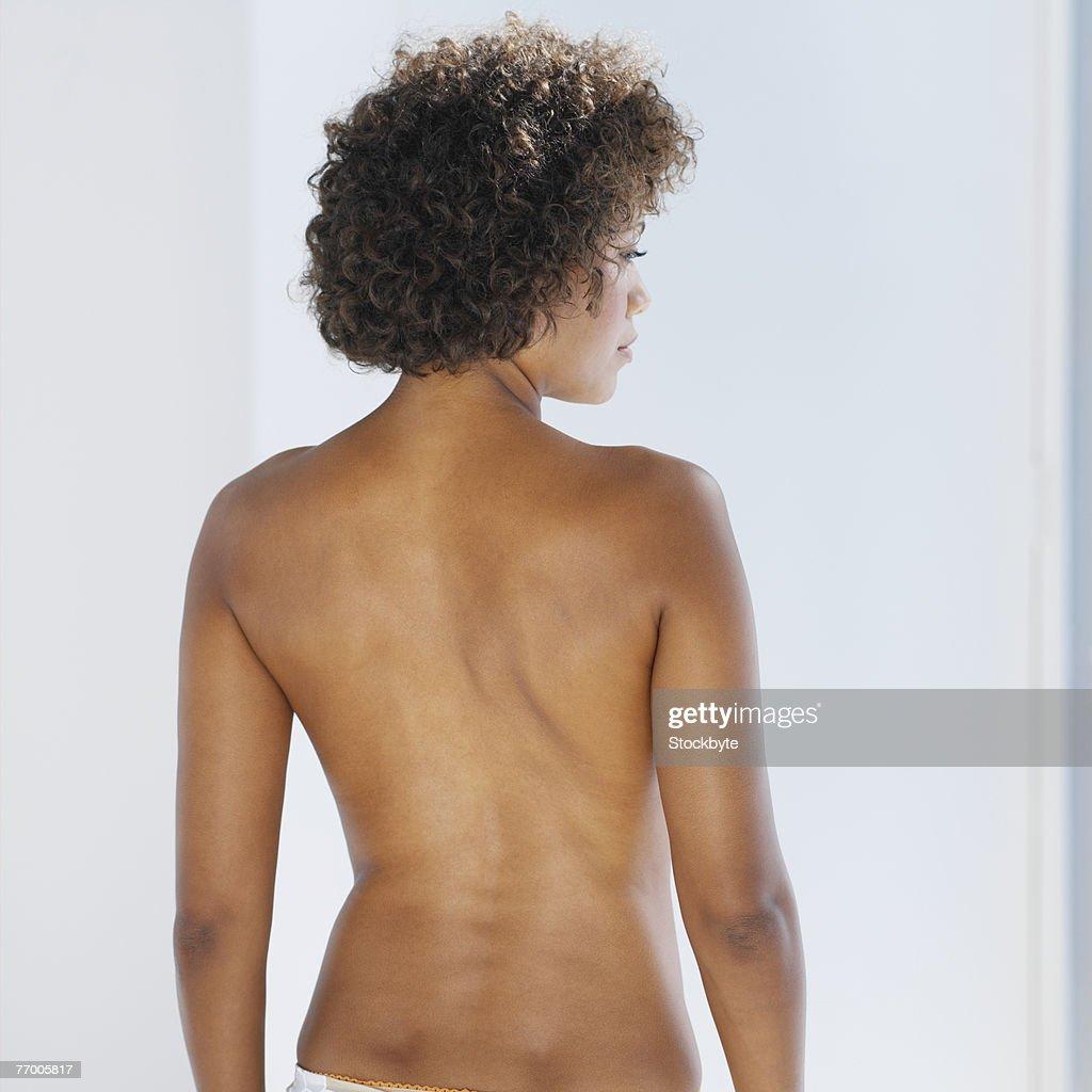 Semi dressed woman, rear view, waist up : Stock Photo