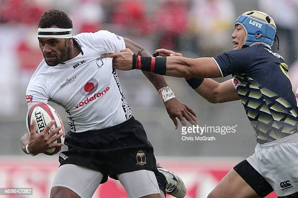 Semi Kunatani of Fiji fends off Yoshikazu Fujita of Japan during the match between Fiji and Japan on day two of the Tokyo Sevens Rugby 2015 at...