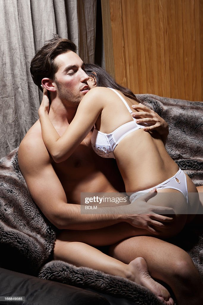 naked couple kissing couch