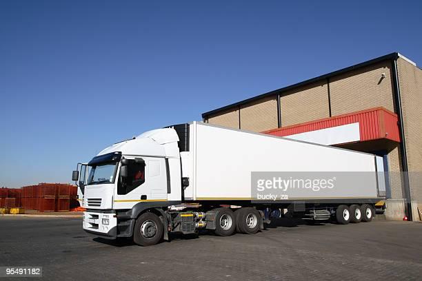 Semi truck at storage warehouse .