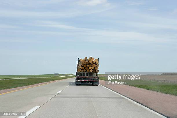 Semi truck hauling timber on highway, rear view