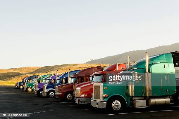 Semi trucks lined up in parking lot
