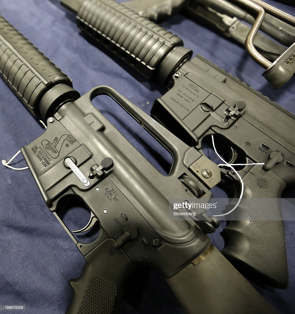 A semi-automatic assault rifle made by Bushmaster Firearms International LLC, left, is displayed for sale at the Rocky Mountain Gun Show in Sandy, Utah, U.S., on Saturday, Jan. 5, 2013. A working group led by Vice President Joe Biden is seriously considering measures that would require universal background checks for firearm buyers, track the movement and sale of weapons through a national database, strengthen mental health checks and stiffen penalties for carrying guns near schools or giving them to minors. Photographer: George Frey/Bloomberg via Getty Images