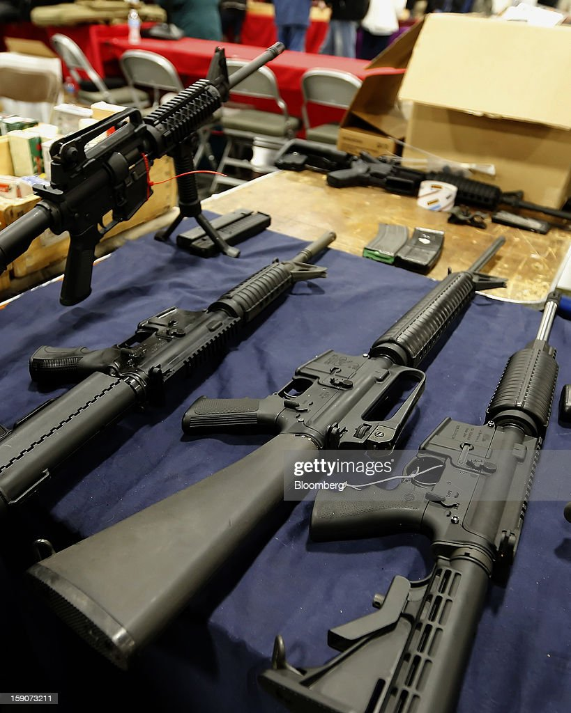 A semi-automatic assault rifle made by Bushmaster Firearms International LLC, , center, is displayed with other guns for sale at the Rocky Mountain Gun Show in Sandy, Utah, U.S., on Saturday, Jan. 5, 2013. A working group led by Vice President Joe Biden is seriously considering measures that would require universal background checks for firearm buyers, track the movement and sale of weapons through a national database, strengthen mental health checks and stiffen penalties for carrying guns near schools or giving them to minors. Photographer: George Frey/Bloomberg via Getty Images