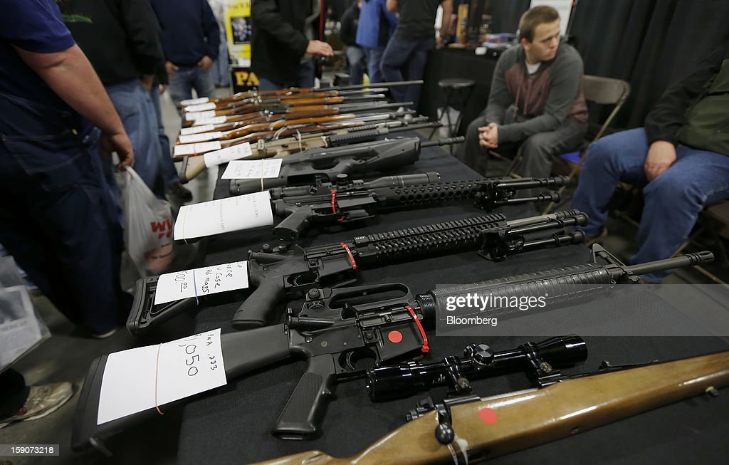 A semiautomatic assault rifle made by Bushmaster Firearms International LLC third from bottom is displayed for sale at the Rocky Mountain Gun Show in...