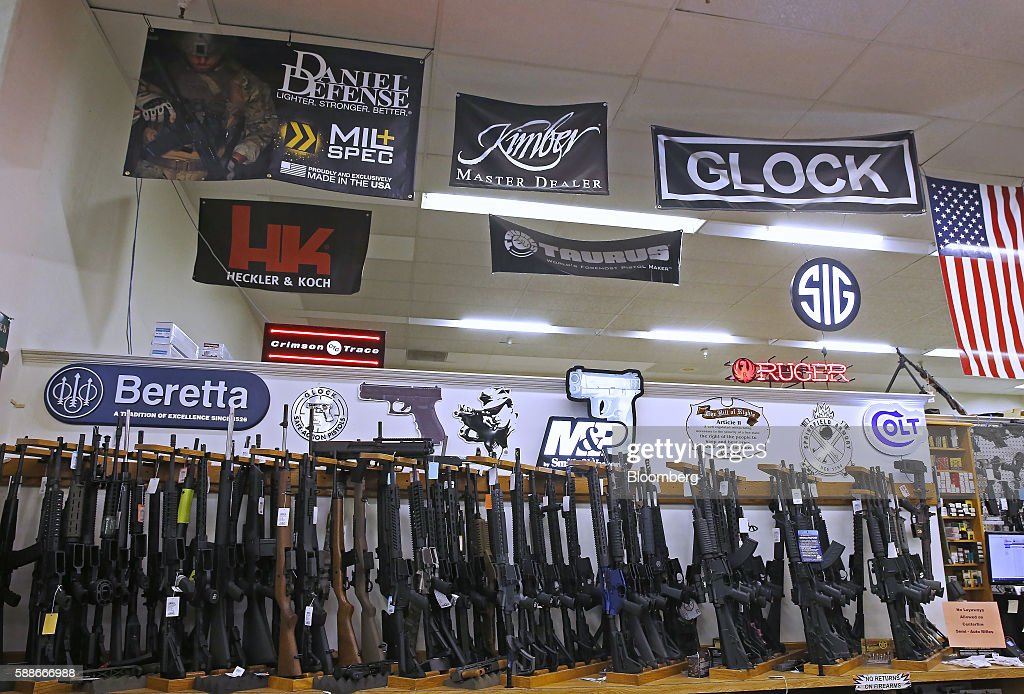 Semiautomatic long guns sit on display for sale below manufacturer advertisements at a gun store in Orem Utah US on Thursday Aug 11 2016 The...