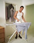 Semi-dressed businessman ironing shirt