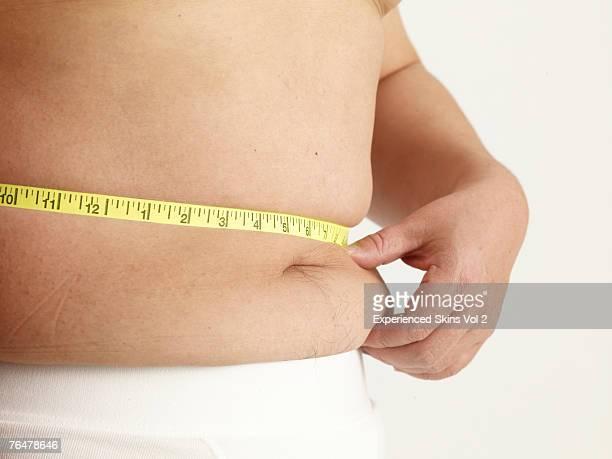 Semi-naked man pinching his stomach