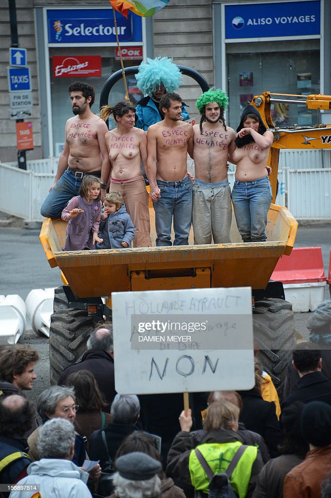 Semi-naked people with words reading 'endangered species' on their chests stand on a dump truck during a demonstration on November 24, 2012 in Nantes, western France, to protest against a project to build an international airport, in Notre-Dame-des-Landes near Nantes. The airport, which is scheduled to replace the current airport at Nantes in 2017, is a pet project of Socialist Prime Minister Jean-Marc Ayrault, who was the city's mayor from 1989 until this year. Among protesters a placard reads 'Hollande, Ayrault, have the courage to say no'.